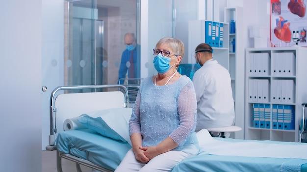 Портрет пожилой женщины, сидящей на больничной койке во время кризиса covid-19. врач и пациенты в защитных масках и снаряжении в современном частном кинозале. система здравоохранения после коронавируса