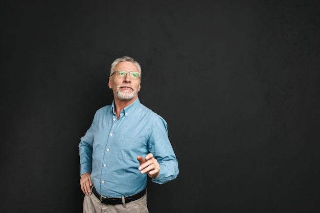 灰色の髪とひげのフォーマルな服と眼鏡を着て黒い壁に分離された意味のある視線で上向きに見ている老人男性70年代の肖像画