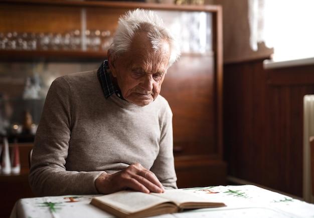 自宅の屋内のテーブルに座って、休んでいる老人の肖像画。