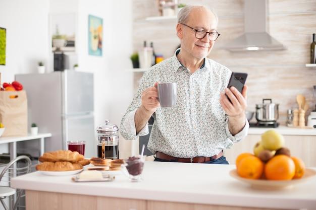 キッチンで現代のスマートフォンを使用しながら笑っている老人の肖像画。インターネットオンラインチャットテクノロジービデオウェブカメラビデオ通話接続カメラ通信電話会議