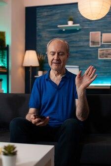 ビデオ通話会議のために手を振っている老人の肖像画