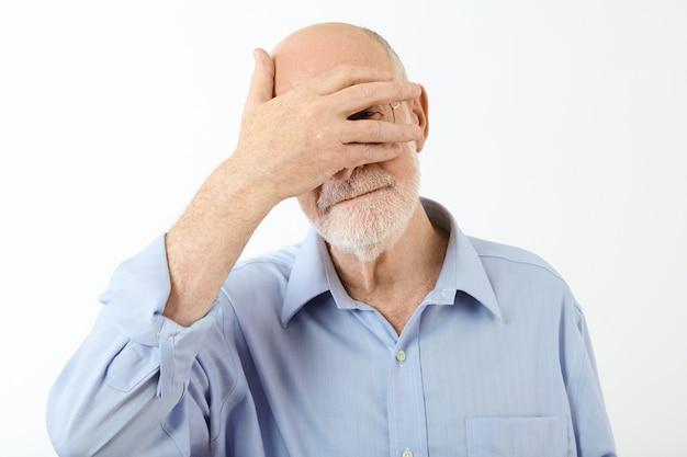 彼の顔に手をつないで、目を覆い、分割された指から覗き見、恥ずかしさを感じて、青いシャツを着た年配の引退した白人男性の肖像画。人間の表情とボディーランゲージ