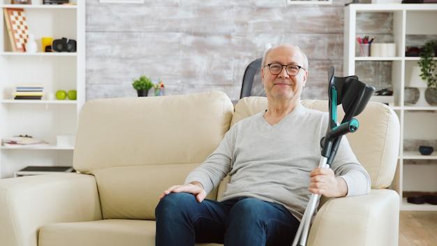 아늑한 요양원에서 카메라를 향해 웃고 있는 은퇴한 노인의 초상화, 그는 소파 옆에 목발을 짚고 있다