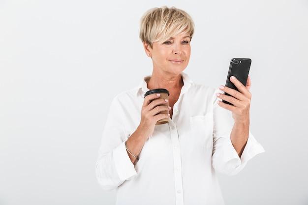 スタジオで白い壁の上に分離された携帯電話と持ち帰りのコーヒーカップを保持している短いブロンドの髪を持つエレガントな大人の女性の肖像画