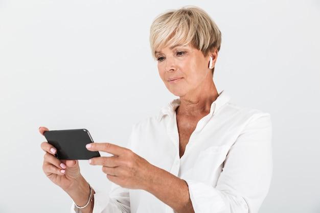 イヤポッドを身に着けて、スタジオで白い壁に隔離された携帯電話を保持している短いブロンドの髪を持つエレガントな大人の女性の肖像画