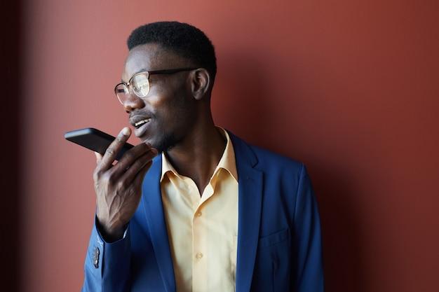 스마트 폰을 통해 음성 메시지를 녹음하고 적갈색 배경에 포즈를 취하는 동안 안경을 착용하는 우아한 아프리카 계 미국인 남자의 초상화, 복사 공간