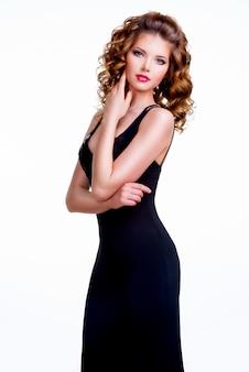 얼굴 근처 손으로 검은 드레스에 우아한 아름 다운 여자의 초상화-흰색 배경에 고립