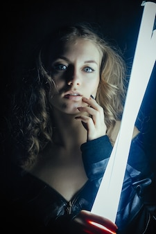 빛나는 네온 불빛 주위에 포즈 빨간 가죽 재킷 유행 정장에 열린 어깨를 가진 우아한 아름다운 여자의 초상화
