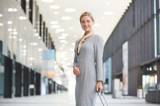 Портрет элегантной блондинки-стюардессы с чемоданом и улыбающейся, позируя в аэропорту,