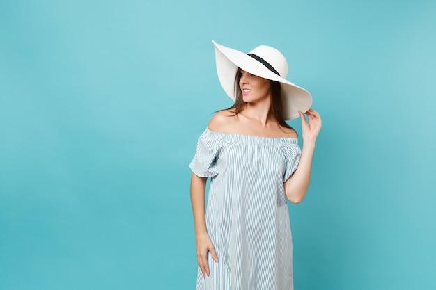 エレガントなファッションの肖像画白い夏の大きな広いつばの日よけ帽、ドレスは頭に手を置き、青いパステルカラーの背景で隔離のコピースペースを脇に見てください。ライフスタイルのコンセプト。