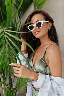 셔츠와 안경을 쓰고 긴 머리를 가진 유행 bodysuit에서 우아한 유행 유럽 여자의 초상화. 손바닥으로 포즈 섹시 한 여자 나뭇잎.