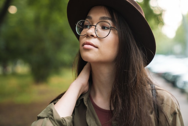 緑の公園を歩くスタイリッシュな帽子と眼鏡を身に着けている長い黒髪のエレガントなゴージャスな女性の肖像画