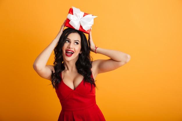 빨간 벽에 우아한 사랑스러운 여자 20 대의 초상화는 노란색 벽 위에 절연 생일 선물 상자를 받고 기쁨을 복용