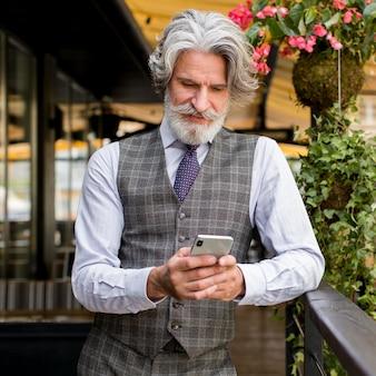 エレガントな成熟した男性保持電話の肖像画