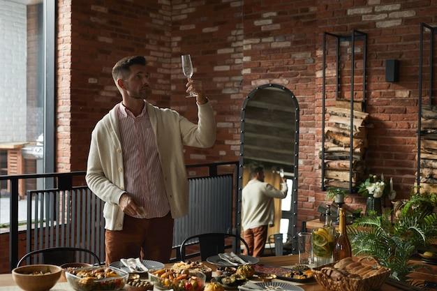 집에서 추수 감사절 파티를 위해 저녁 식사 테이블을 제공하는 동안 안경을 검사하는 우아한 성숙한 남자의 초상화,
