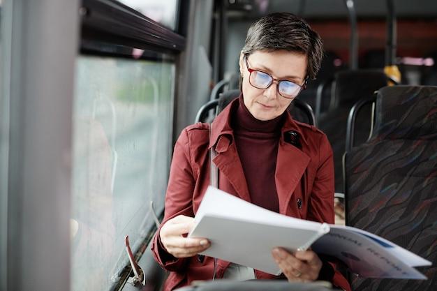 Портрет элегантной зрелой женщины, читающей книгу в автобусе во время поездки на общественном транспорте по городу, копией пространства