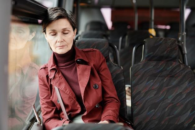 Портрет элегантной зрелой женщины, спящей в автобусе во время поездки на общественном транспорте по городу, копией пространства