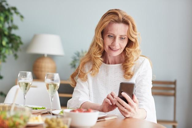 自宅で夕食を楽しみながらスマートフォンを使用して、エレガントな成熟した女性の肖像画、コピースペース
