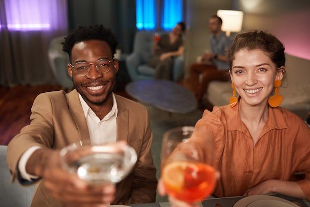 실내에서 친구들과 저녁 식사를 즐기고 카메라에 건배하는 우아한 혼혈 부부의 초상화