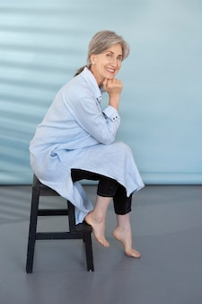 ポーズをとって幸せであるエレガントな年上の女性の肖像画