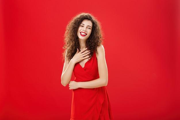 赤い背景の上にエレガントなイブニングドレスでポーズをとって笑って笑って笑って胸に手のひらを保持している巻き毛の髪型を持つエレガントな満足と感謝の魅力的な白人女性の肖像画。