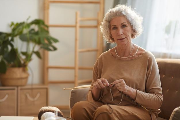 햇빛에 의해 조명 아늑한 집에서 소파에 앉아있는 동안 뜨개질 우아한 수석 여자의 초상화