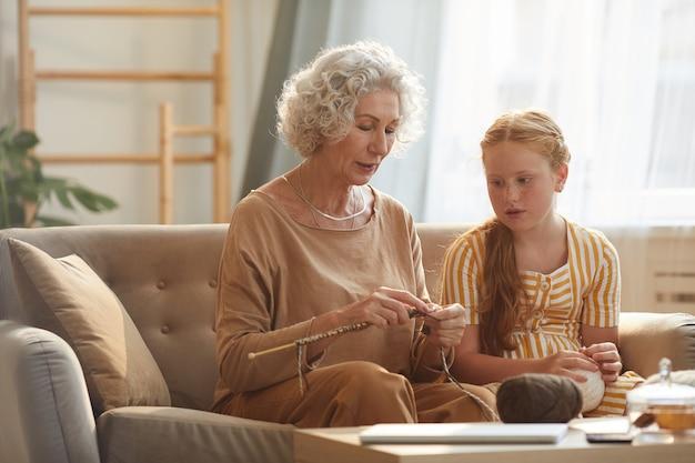 햇빛에 의해 조명 아늑한 집에서 소파에 앉아있는 동안 뜨개질을하는 손녀를 가르치는 우아한 수석 여자의 초상화
