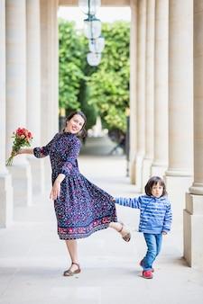 夏に柱のある都市の建物の横に彼女の太陽とポーズをとって青いドレスを着たエレガントな女性の肖像画