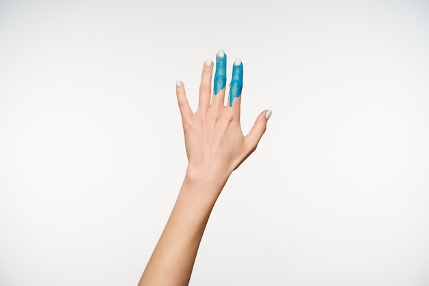 Портрет элегантной женщины с поднятой рукой с синей краской на указательном и среднем пальцах, которая тянет ее вперед, будучи изолированной на белом