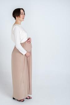 ベージュのドレスでエレガントな若い妊婦の肖像画