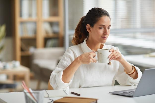 Портрет элегантной молодой женщины, смотрящей на экран ноутбука и пьющей кофе, наслаждаясь работой из дома в минималистичном белом интерьере, копией пространства