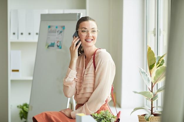 Портрет элегантной молодой женщины разговаривает по телефону, сидя у окна в офисе и весело улыбаясь
