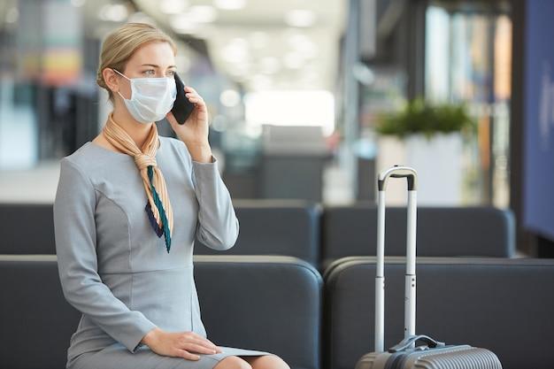 Портрет элегантной молодой женщины в маске и разговора по телефону, сидя на диване в зале ожидания аэропорта,