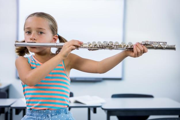 教室でフルートを演奏する小学生の女の子の肖像画