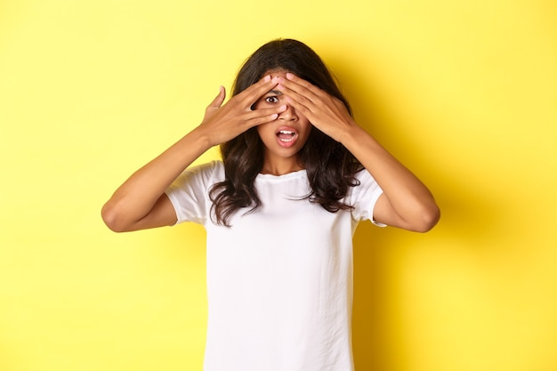 Портрет смущенной и шокированной афроамериканской девушки закрыл глаза, но выглядывал сквозь пальцы