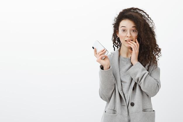 Портрет смущенной симпатичной кудрявой студентки в стильном сером пальто и очках, держащей смартфон, поднимающей брови и кусающей палец