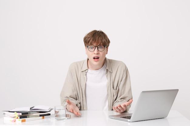 Портрет смущенного шокированного молодого человека-студента в бежевой рубашке и очках выглядит смущенным, сидя за столом с портативным компьютером и ноутбуками, изолированными над белой стеной