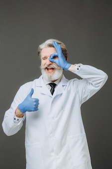 Портрет эмоционального доктора на серой стене. седой доктор сеньор одет в белое пальто и синие перчатки, изолированные на сером фоне.
