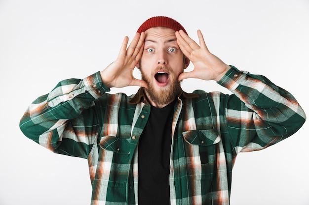 Портрет эмоционального парня в шляпе и клетчатой рубашке, кричащего, стоя изолированно на белом фоне
