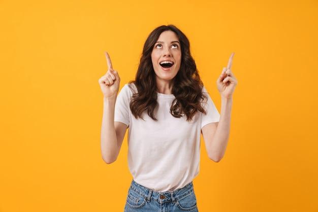 Портрет эмоциональной счастливой удивленной молодой женщины представляя изолированной над желтой указывать стены.