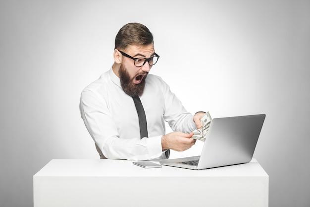 Портрет эмоционально потрясенного бизнесмена в белой рубашке сидит в офисе, держа деньги с удивленным лицом и открытым ртом, глядя на ноутбук. крытая студия выстрел, изолированные на сером фоне.