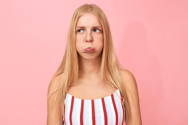 똑바로 공정한 머리를 가진 감정적 인 불행한 젊은 백인 여자의 초상화 화가 표정으로 뺨을 피고, 입이 공기로 부풀어 오르고 입술이 부풀어 오른다.