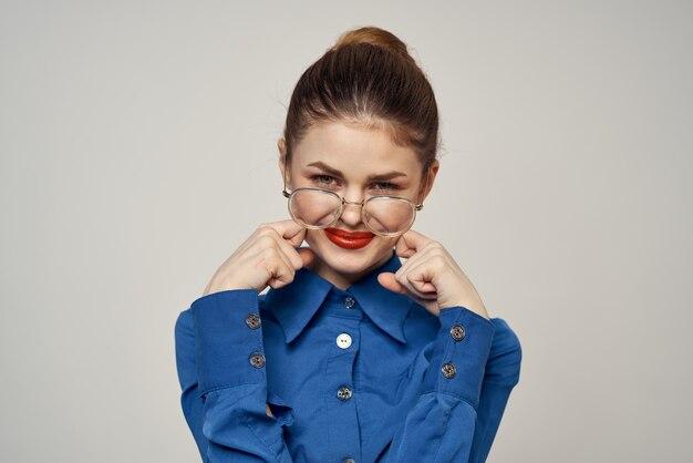 青いシャツとメガネの明るいメイクモデルライトで感情的な女性の肖像画