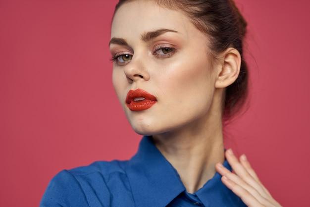 Портрет эмоциональной женщины в синей рубашке с ярким макияжем, жестикулирующим руками copy space