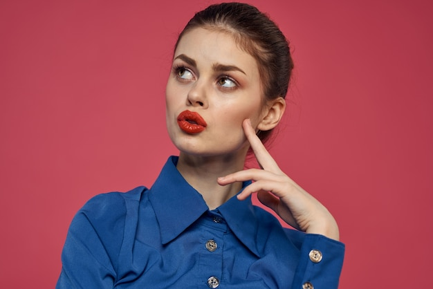手で身振りで示す明るい化粧と青いシャツの感情的な女性の肖像画