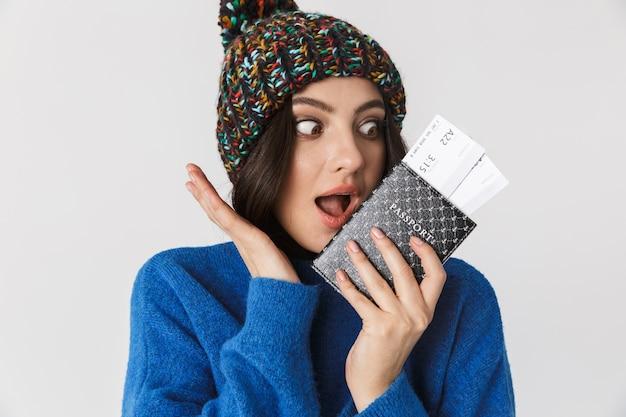 Портрет эмоциональной женщины в зимней шапке, держащей паспорт и проездные билеты стоя, изолированную на белом