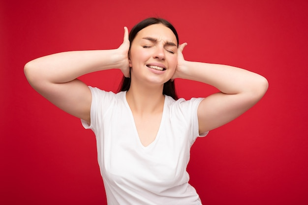 空のスペースと耳を覆う赤い背景の上に分離されたモックアップの白いtシャツを着て誠実な感情を持つ感情的な若い魅力的なかなりブルネットの女性の肖像画。