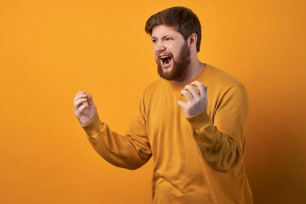 感情的なイライラしたイライラした無精ひげを生やした男性の肖像画は、妻と議論しながら怒って歯を食いしばり、ジェスチャーをします