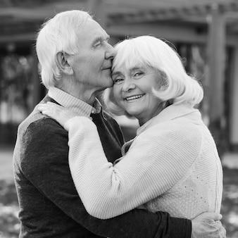 끝없는 사랑의 초상화. 야외 및 집 앞에 서 있는 동안 서로 결합하고 웃고 있는 행복한 노부부의 흑백 초상화