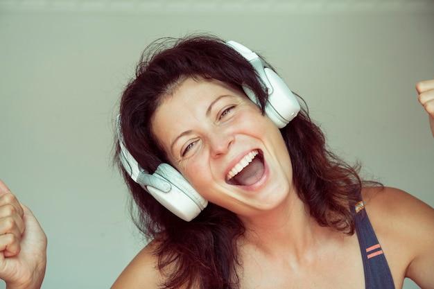 ヘッドフォンでエネルギッシュなブルネットの若い女性の肖像画は、音楽を聴いて楽しんでいます。
